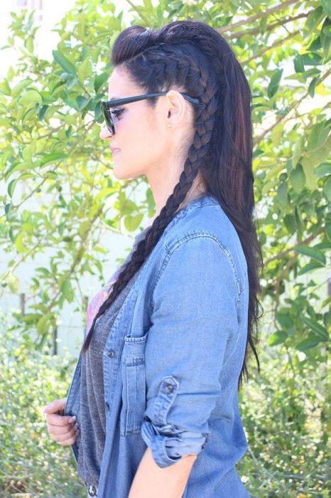 Chica de cabello negro con una trenza de lado, usando una chamarra de mezclilla blusa gris y lentes negros