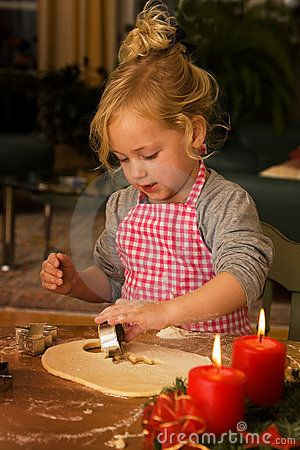 Child bakes Christmas cookies in Advent