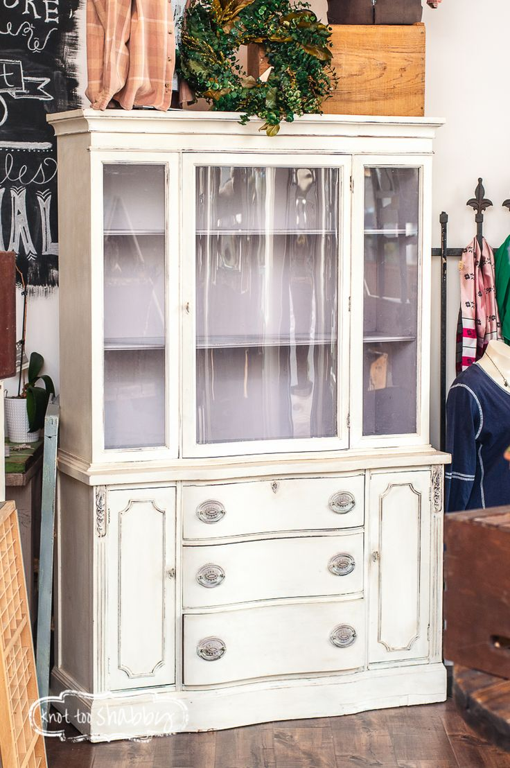 This is a beautiful and structurally sound china cabinet, likely dating back to the 1930's or 40's. The outside has been refinished with Chalk Paint® by Annie Sloan in a soft and lovely neutral, Old White. A soft shading of dark wax allows the details and curves to pop while adding a richness and depth of color. The inside is painted in Paloma, a soft grey with lilac undertones.