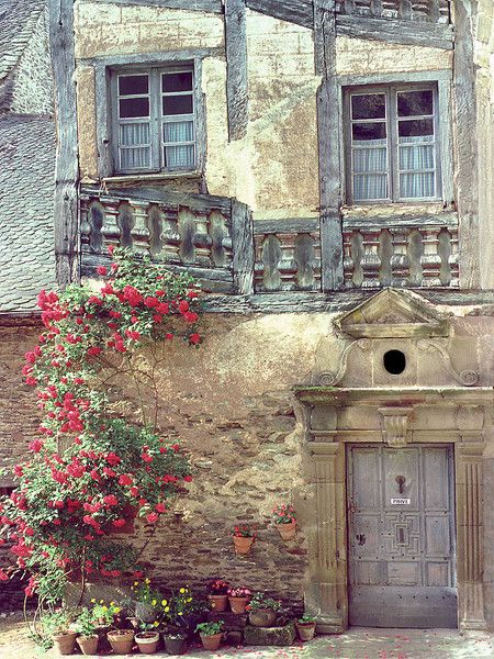 European photo of medieval building with flowers in Conques(Aveyron), France by Dennis Barloga