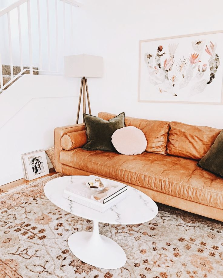 living room | modern | white table | brown leather sofa | couch | artwork | staircase | stairs | floral rug