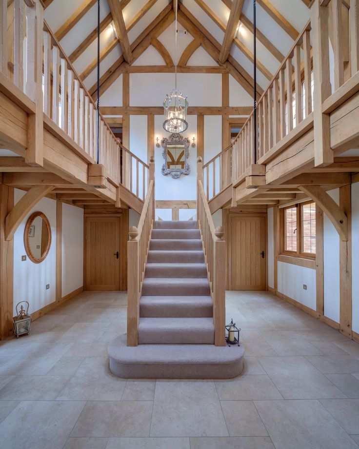 A welsh Oak Frame house with a light and airy oak hallway with beautiful oak staircase and high ceilings. #oak #stairs #purlin #trusses #airy #light #welshoakframe