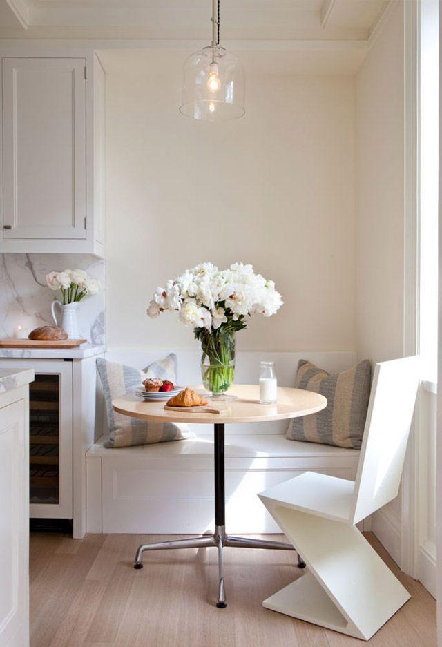 Adosada al muro una pequeña banqueta como continuación de la cocina, en madera laminada blanca, dos cojines en tonos celeste y crema, una mesa redonda de patas metálicas y silla de madera blanca de una sola pieza con patas en Z.