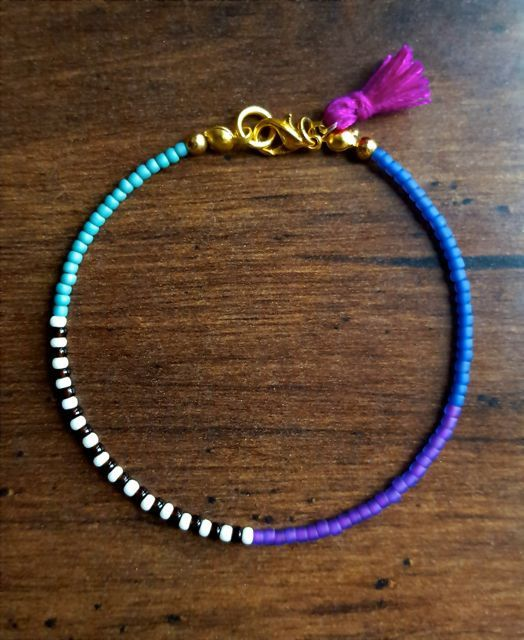 Radiate bohemian vibes with this awesome seed bead bracelet! Created with glass seed beads in neon purple, aqua, indigo, cream, and black; a bright + tiny purple tassel; and finished with a dainty lit
