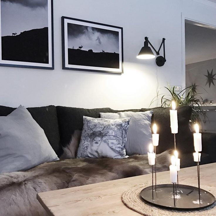 Scandinavian living room with fur, wood, lit candles at framed black and white posters from printler.com, the marketplace for photo art. Interior design by lapptussan at instagram.