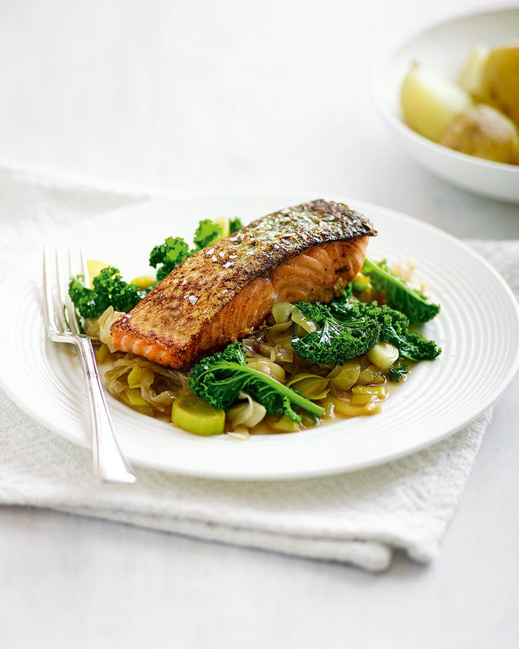 Pan-fried salmon sits on a bed of sweet-and-sour leeks and lightly crisped kale in this healthy midweek recipe.