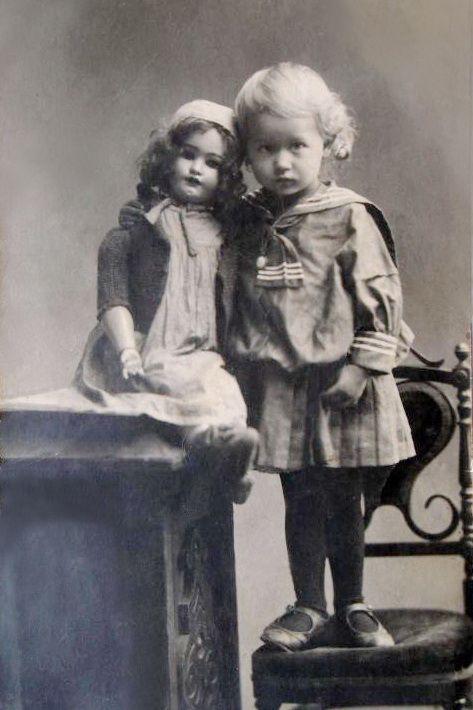 A sullen little girl in a sailor dress with her large doll.