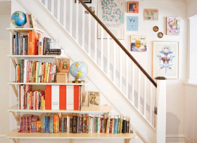 Make use of your home's existing features. These bookshelves mimic the stairway behind them.
