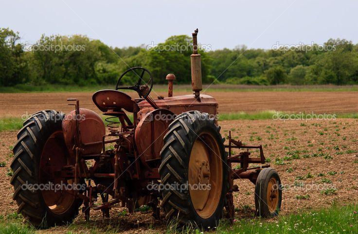 Vieux tracteur rouillé rouge au bord d'un champ