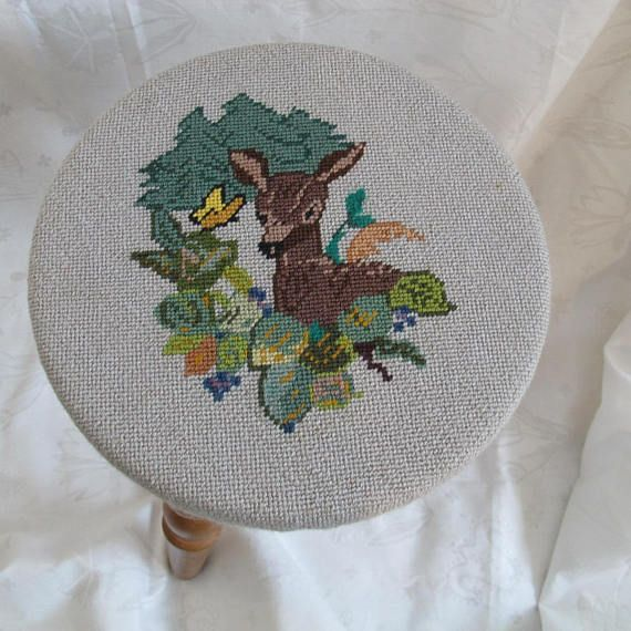 This isnt your traditional needlepointed footstool! This adorable vintage footstool features a Bambi like deer. Hand needlepointed and in very good condition. Seat is just over 10 inches in diameter by 1 1/2 inches thick - unpadded. About 11 1/2 inches tall. Turned maple legs. Legs are