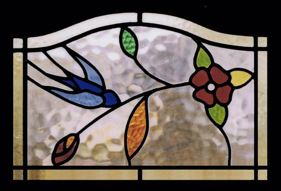 Antique Stained Glass Window featuring a bluebird discovered at Scottish Stained Glass. This company specializes in window restoration.