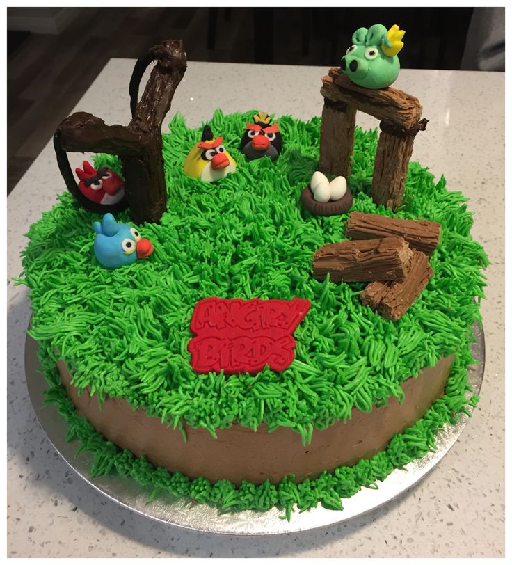 Angry Birds cake - slingshot made out of twix bars and forts made using flakes. Little fondant figurines made by my daughter :)