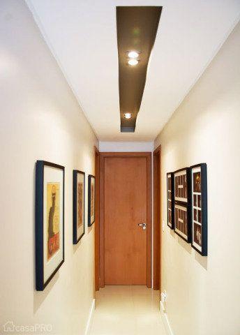 Neste projeto foi utilizado o recurso do forro de gesso rebaixado para criar um rasgo contínuo com iluminação embutida. O fundo dele foi pintado com uma cor mais escura, para criar um efeito mais cênico. Nas paredes, quadros, pôsteres de viagens e fotos dos proprietários do apartamento. A ideia do corredor com estilo é que as pessoas possam apreciá-lo enquanto caminham. Projeto de Aline Dal´Pizzol.