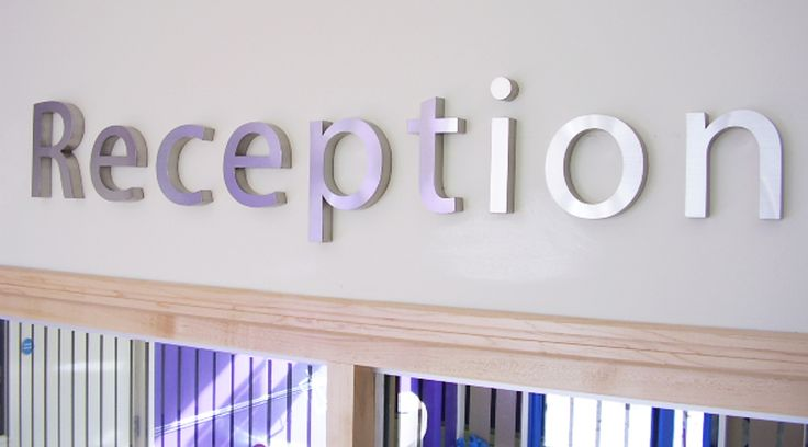 3D stainless steel 'Reception' signage applied to wall above reception desk. By Space3.co.uk
