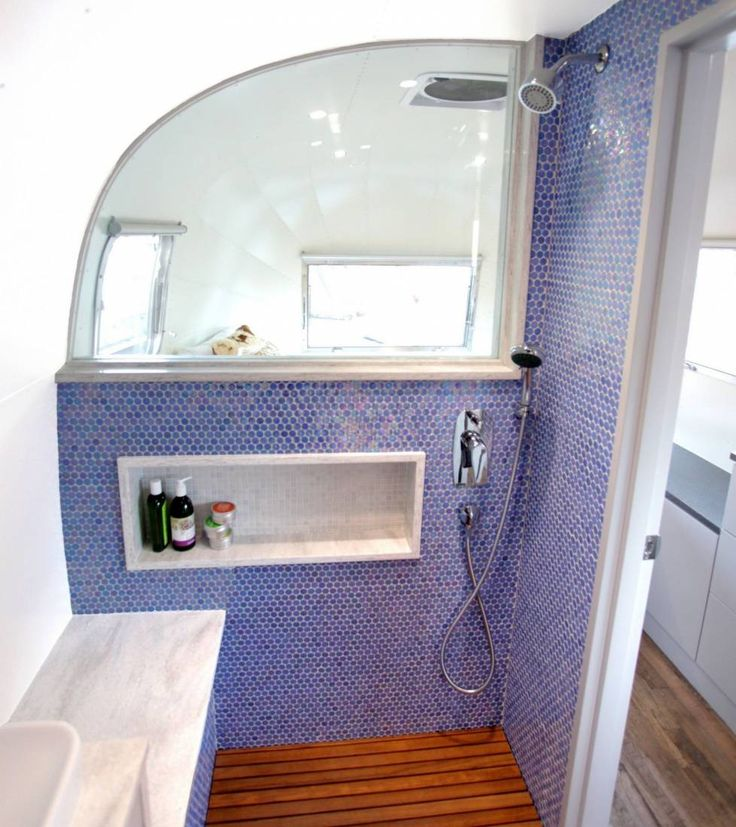Luna Blue Moon Trailer Airstream Bathroom shower wood floor tile walls window sing counters shampoo