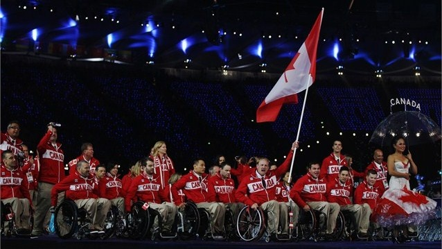 Wheelchair Rugby player Garrett Hichling of Canada carries his national flag during the Athletes' Parade at the Olympic Stadium.