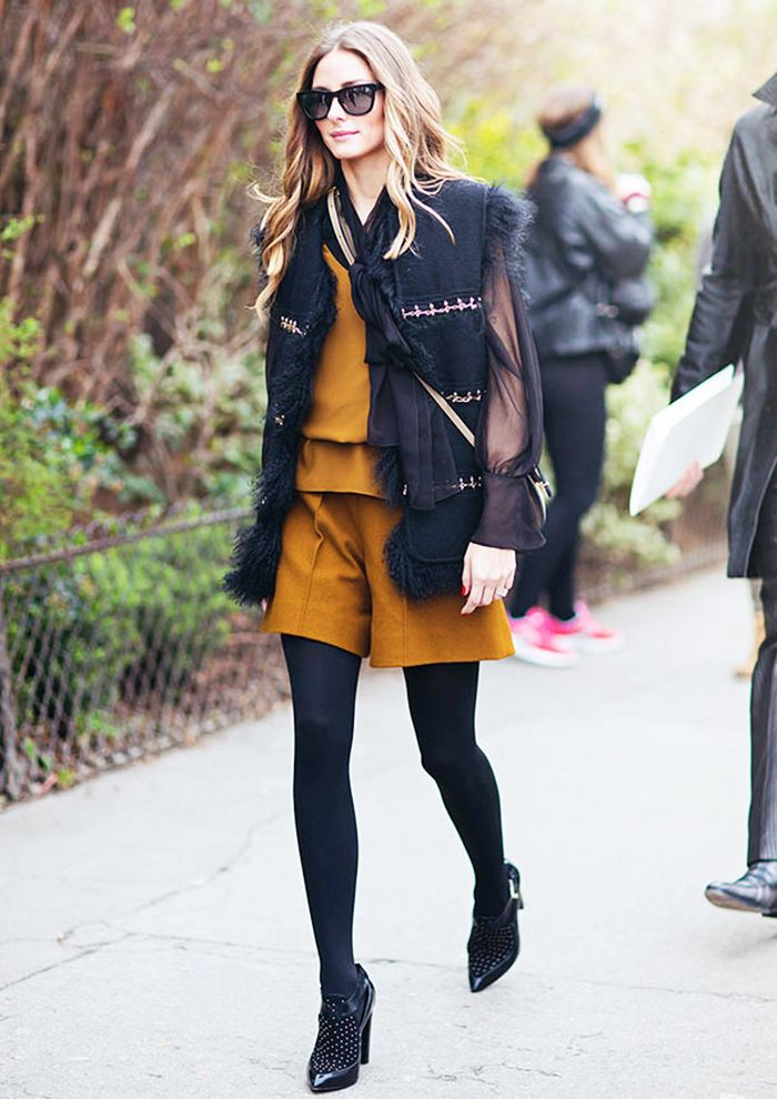 Olivia Palermo in a vest, matching mustard top and shorts, black tights, and studded heels
