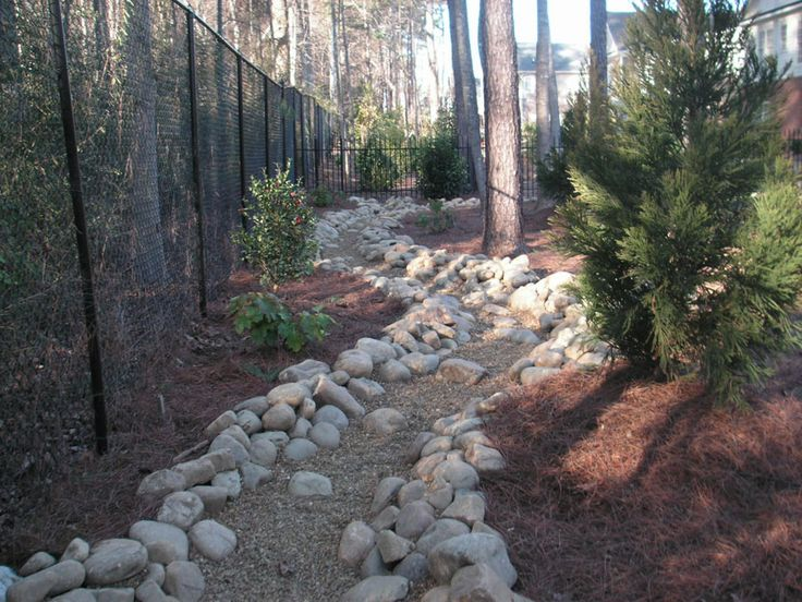 80 Foot Long Bed Constructed Of Multiple Sized River Rock And Boulders  Through Landscaped Woodland Garden.