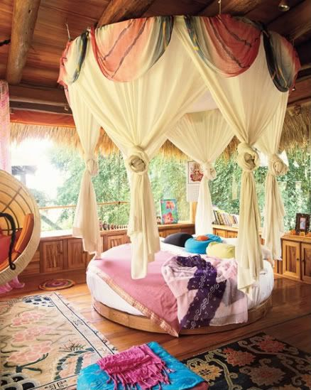 use of turquioise/purple, circular bed and harem canopy in a room backdropped by nature is blissful indeed.