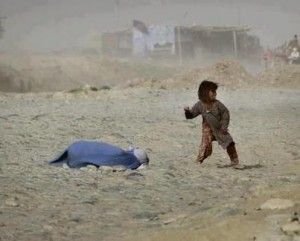 A little girl trying to defend her mother after she has been stoned to death . Sadly she is too late