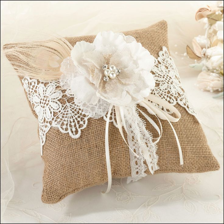 Burlap wedding ring pillow finished with lace, ribbons and a flower with crystal detailing.