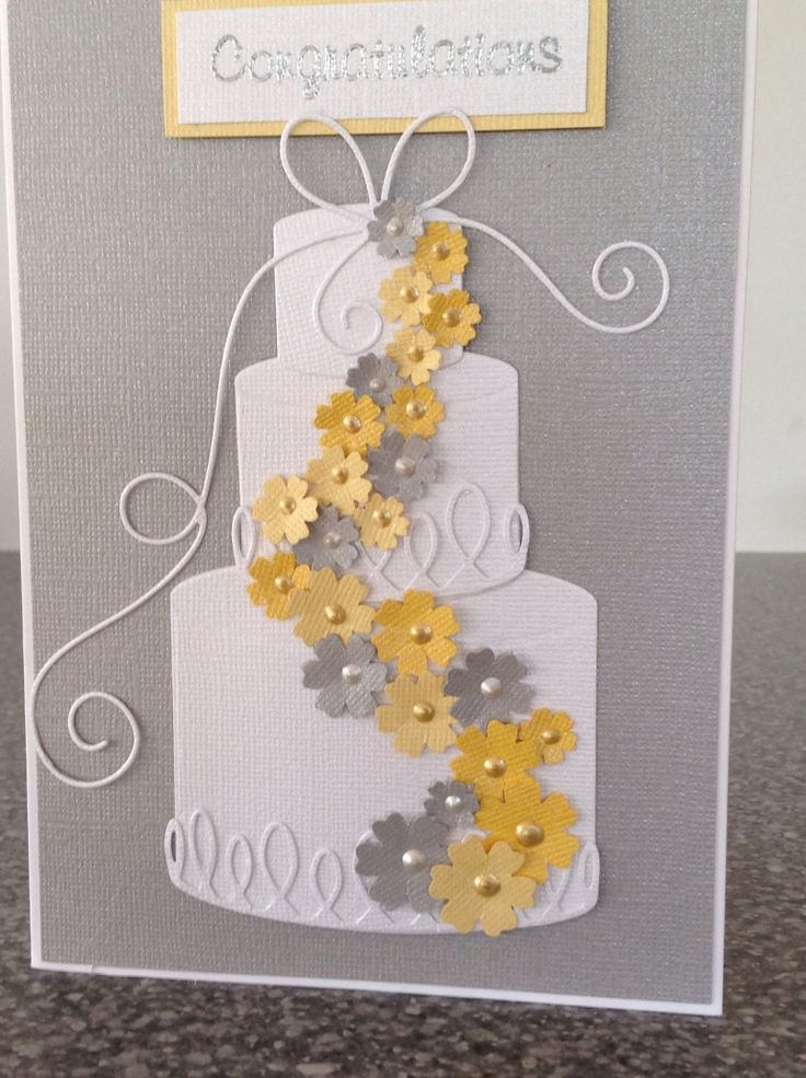 handcrafted wedding card ... gray/silver card base ... magnificent cake die from Memory Box ... white cake with bow & flourishes ... stream of yellow and gray flowers winds down from top ... clean, graphic look ... like the little dots of pearl in all the flower centers  ... great card!!