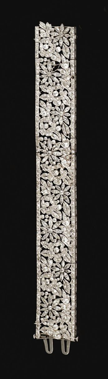 DIAMOND BRACELET, FRENCH, CIRCA 1915. The articulated open work band decorated with floral and foliate motifs, millegrain-set with triangular, circular-, step-cut and marquise- shaped diamonds, to an engraved gallery, mounted in platinum. French assay and maker's marks.