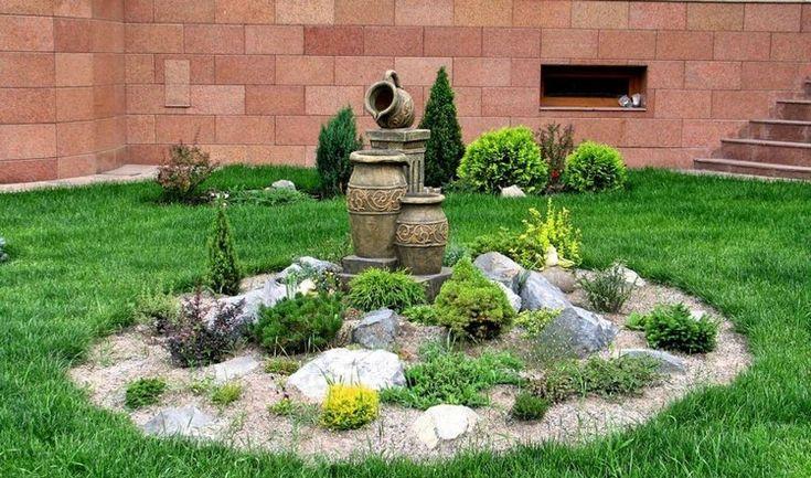 jardin alpin avec plantes tapissantes, gazon, conifères, arbustes et déco en pierre naturelle
