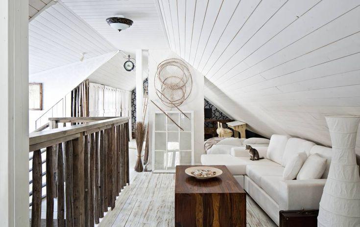 Yläkerran oleskelutila ja makuu-huone ovat lähes yhtenäistä, avointa tilaa. Hormiseinälle on ripustettu papan vanha rysä ja seinään nojaa talosta löytynyt vanha ikkuna. Paperivalaisin on ostettu Ikeasta. Sohva on Suomi-Soffan mallistosta ja pöytä Maskusta. Pieni Spiidi-kissa istuskelee sohvalla.