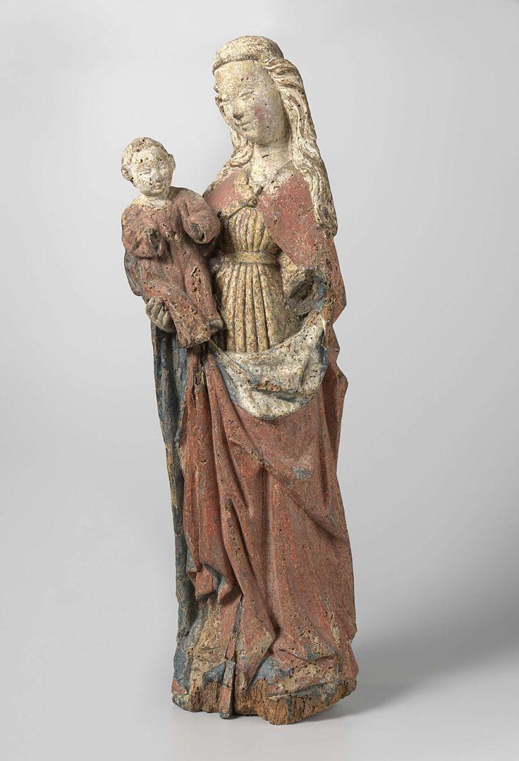 Anonymous | Maria met kind, Anonymous, c. 1450 | Maria staat met de linkerknie iets naar voren. Het hoofd is iets opzij gericht, naar het kind, dat zij op de rechterarm draagt. Het kind is gekleed in een lang hemd en houdt zijn armen naar voren. Maria draagt een band in het bij de slapen uitstaande en over de schouders vallende haar. Over het geplooide en door een ceintuur samengesnoerde kleed draagt zij een wijde tot op de grond afhangende mantel. Deze wordt voor de borst door een agrave…