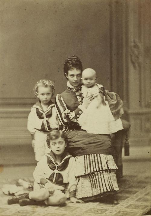 Tsarina Maria Feodorovna of Russia, nee Princess Dagmar of Denmark, with her children; Tsarevich Nicholas (sitting on floor), Grand Duke George (standing behind Nicholas), and Grand Duchess Xenia (held)