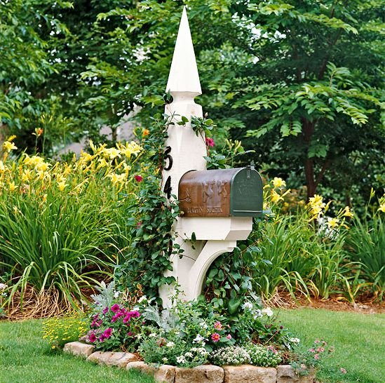 copper mailbox on white mailbox post with beautiful landscaping via BHG