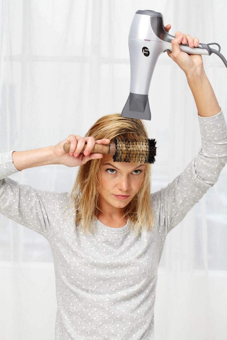 Step 2: If you have bangs, blow-dry them using a big, round brush. Pull them straight out from your forehead and aim the dryer's nozzle toward their ends. Fernando Milani  - Redbook.com