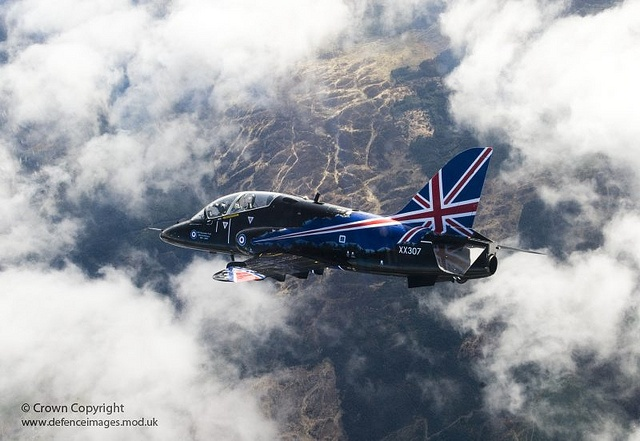A specially painted Hawk T1 jet aircraft of the Royal Air Force's 208 Squadron, is pictured flying through the clouds over its home at RAF Valley in Wales.