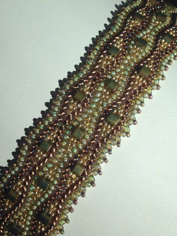 Waves of shimmering copper-lined amethyst AB seed beads and aqua lined topaz seeds ripple their way along the entire length of this intricately woven herringbone (also known as Ndebele) bracelet. Caught up in the waves are frosty matte khaki Miyuki 4mm cubes nested in gold Charlotte seeds. It is the striking contrast of finishes that makes this sparkling green and amethyst colorway Absolutely Stunning. Total length of this bracelet, including the antique brass slide clasp is 7 1/2 and it is…