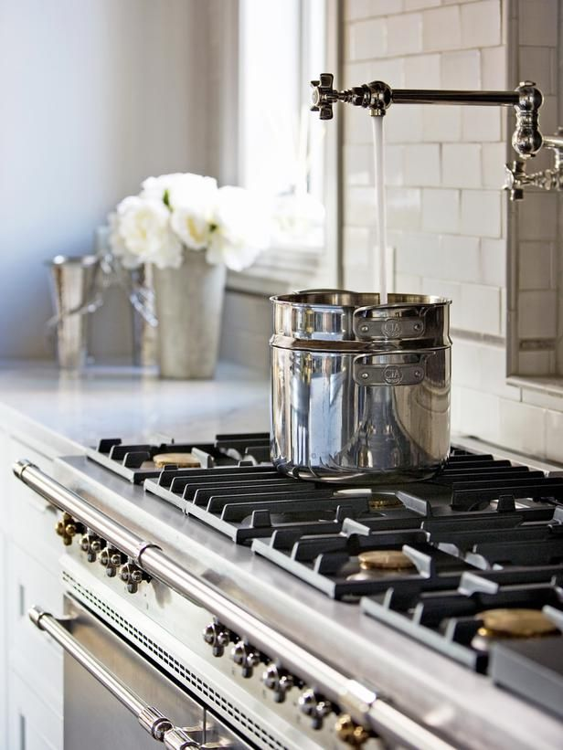 The Lacanche steel and nickel range made in Burgandy, France is the centerpiece of this chef's kitchen. Rohl pot filler and antique iron fireback dating from the 1700s is surrounded by Waterworks and Sonoma Tilemakers tile.