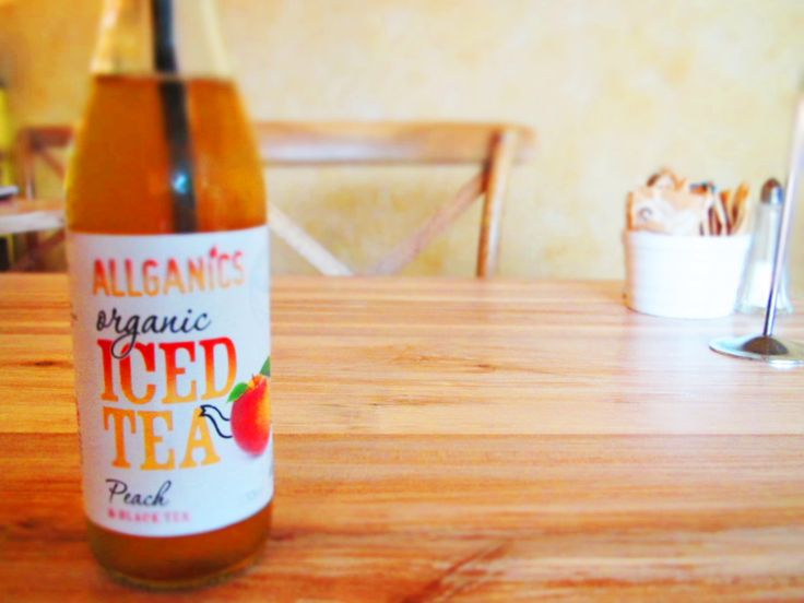 Drinking the delicious Allganics Organic Iced Tea Peach Flavors inside the beautiful cafe The Golden Sands. New Zealand