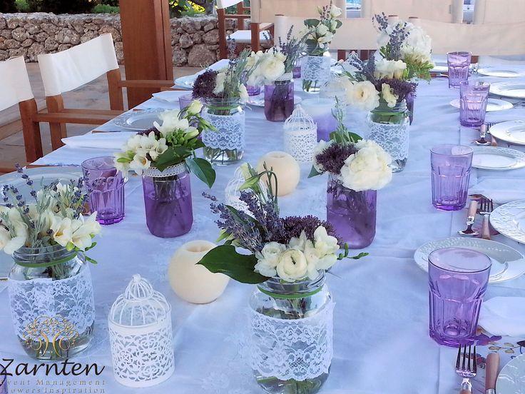 Βάζα με λεβάντα και αγριολούλουδα σε λευκό, μπλε και μωβ ντυμένα με λευκή δαντέλα για διακόσμηση τραπεζιού δεξίωσης. Εντυπωσιακή και ταυτόχρονα ρομαντική διακόσμηση τραπεζιού με λεβάντα, φρέζιες, τραχίλιουμ και νεραγκούλες