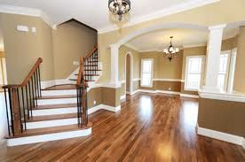 oatmeal and biscuit walls, white trim, dark wood floors and banisters, open plan hall/living rooms