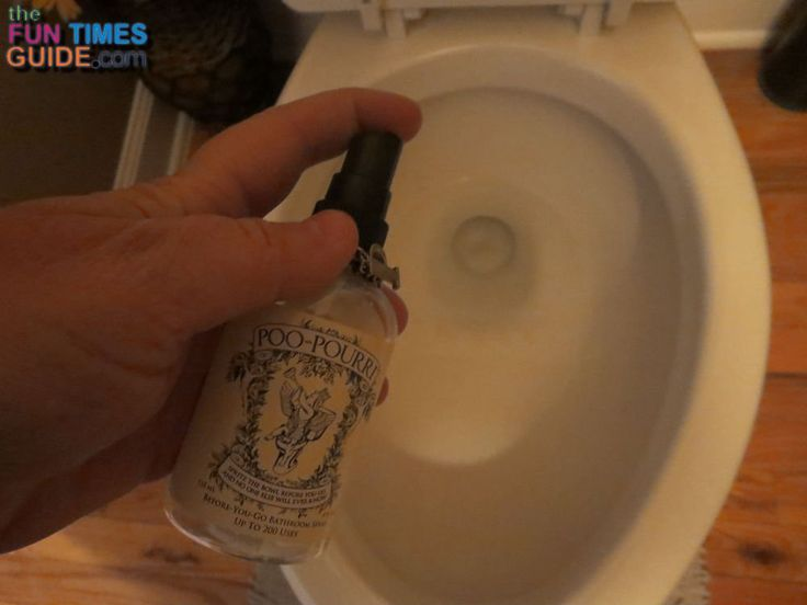 Spraying Poo Pourri poop spray into the toilet bowl. photo by Lynnette at TheFunTImesGuide.com