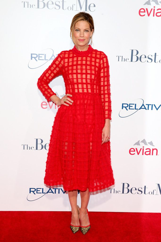 We're looking to actress Michelle Monaghan for tips on how to rock red with ease. Monaghan wore this stunning Simone Rocha brushed-wool check dress from the Fall 2014 collection to the Los Angeles premiere of her new movie, The Best of Me.The dress featured an all-over large checker print, a semi-sheer bodice and a midi-length skirt. The look-at-me red color was vibrant and complemented Monaghan's skin tone. The actress accessorized with red suede, pointed-toe pumps with gold and black mesh…