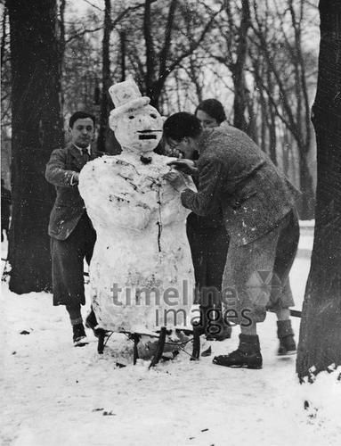 Junge Leute bauen einen Schneemann ullstein bild - ullstein bild/Timeline Images, 1938
