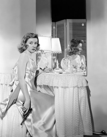 Gloria Graham 1923 – 1981  Posing with every girls essential accessory, a gun