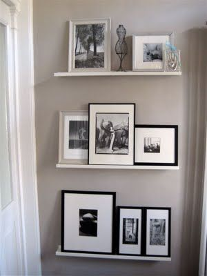 simple white shelving to display black  white photos in a small foyer.