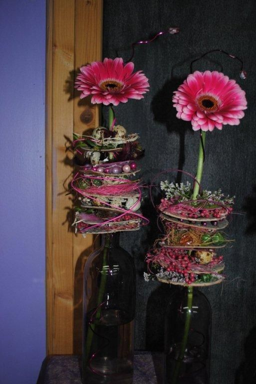 bloemstuk - flessen met boomschors en frutsels en een gerbera ( i.p.v boomschors e.v.t CD's )