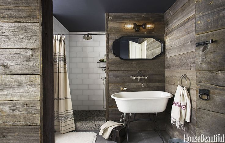 In this Southborough, Massachusetts, country bathroom by Andrew and Yvonne Pojani, the design is all about the warm, reclaimed barn wood on the walls. Roku white glass tile from Walker Zanger adds a contemporary note to an old-fashioned bath. Sumba Speckled pebble tile by Island Stone. Grohe Retro showerhead. Rohl Country faucets. Atomic Topless Double Industrial Guard sconce from Barn Light Electric. Vintage towel ring by Restoration Hardware.   - HouseBeautiful.com