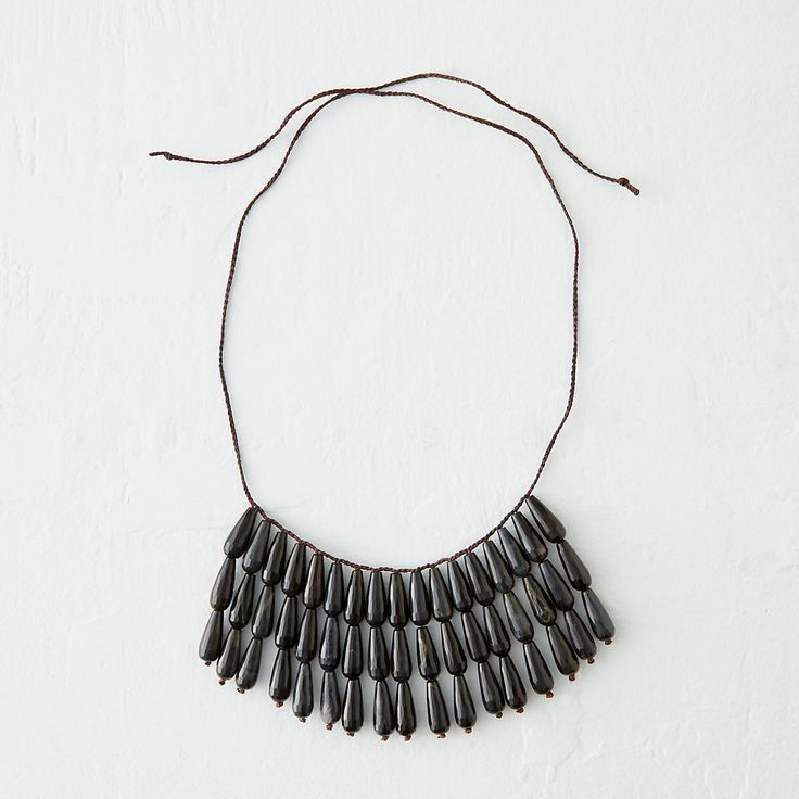 """A triple-layered fringe of faceted, golden eye stones in deep navy forms this statement strand, each one hand-crafted by Connecticut designer Ann Lightfoot.- Golden eye stone, nylon cord- Tie closure- Bib drop: 19.5""""- Pendant: 7""""W, 3""""L- Handmade in the USA35""""L"""