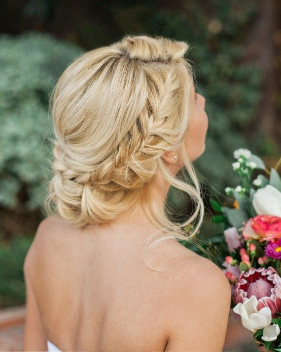 """Brides who are planning a romantic wedding will adore the loose and effortless braids in this updo. """"One tip is to leave wavy strands on both sides of your face for a sexier, sophisticated look,"""" Irving recommends."""