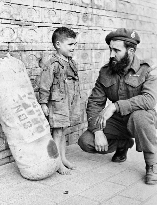 Private J.S.P. Bowen of the Princess Patricia's Canadian Light Infantry (P.P.C.L.I.), says goodbye to a young friend before leaving Italy for a 30 day Christmas leave in Canada; Italy - December 1944.