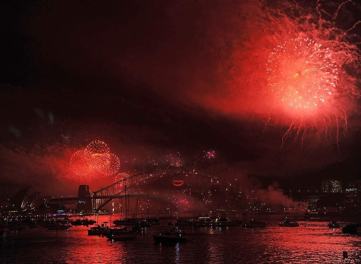Spectator boats in Sydney Harbour look on as New Year's Eve fireworks erupt over the Sydney Harbour Bridge